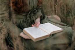 Close-up of a woman holding a book while sitting in the grass