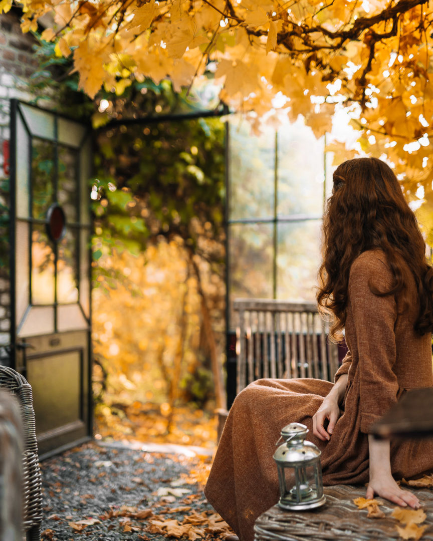 Woman sitting under golden leaves in a winter garden after returning to Aux Quatre Bonniers.