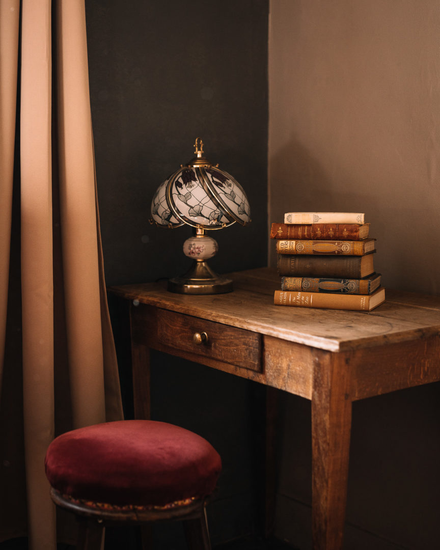 Returning to Aux Quatre Bonniers in the Victor Hugo Suite, with a stack of books and vintage lamp on a table.