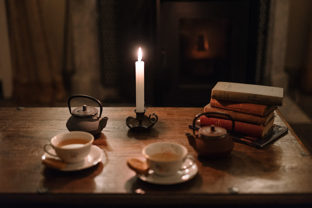 Returning to Aux Quatre Bonniers with a stack of books, tea and biscuits on the table in front of the fire.