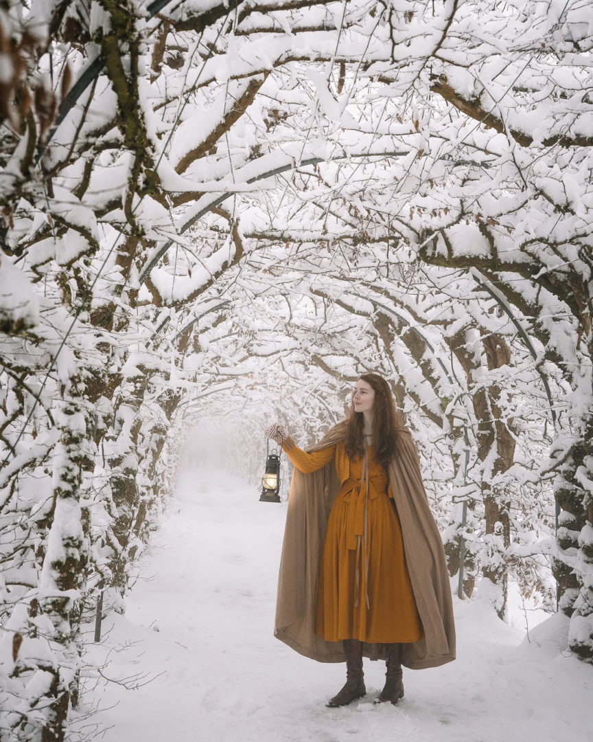 Woman with a lantern walking through the tree tunnel La Charmille
