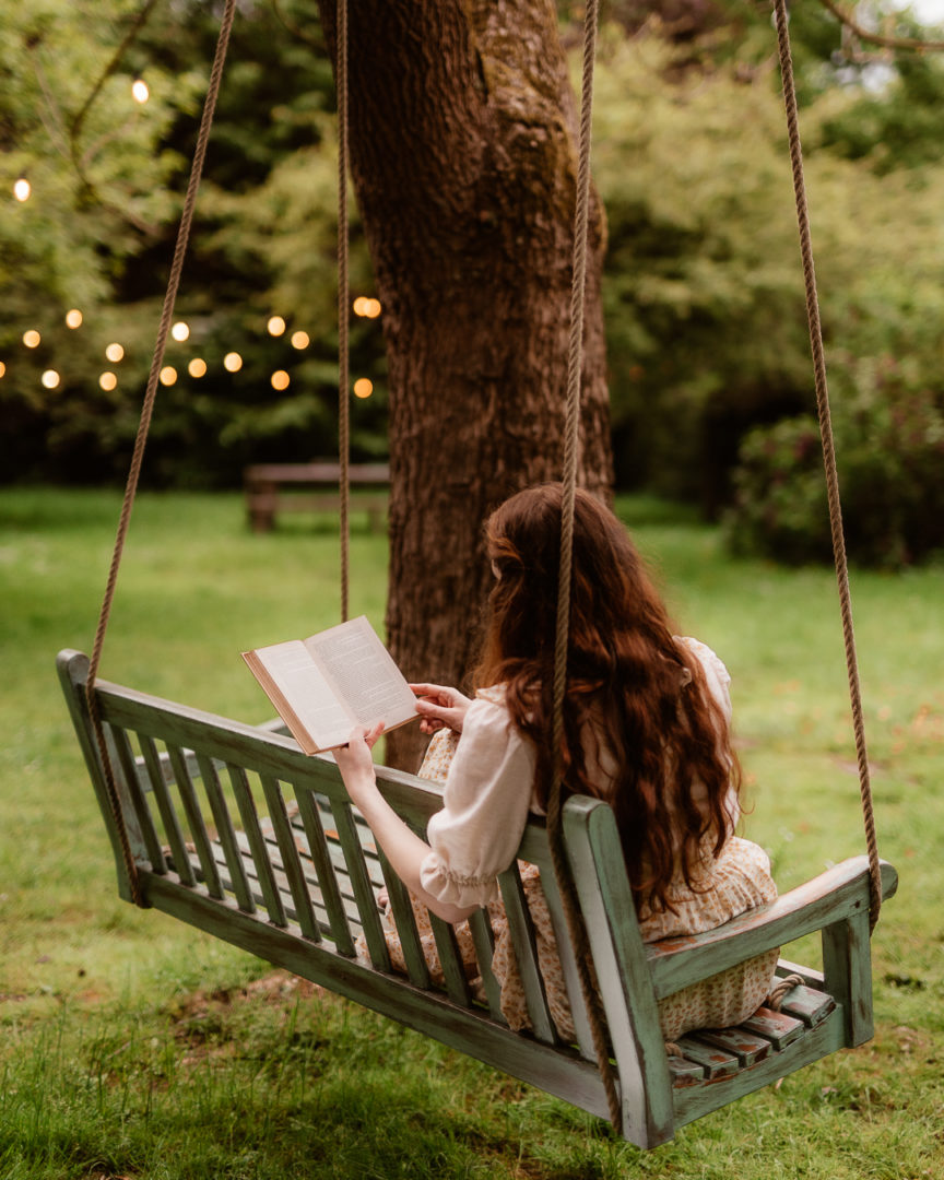 woman reading on a swing in the garden of la petite foret