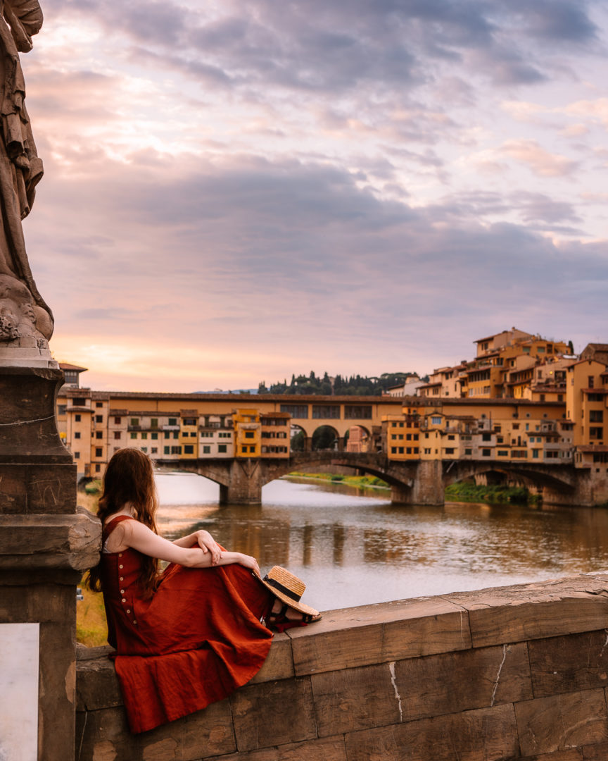 woman sitting on a bridge in florence